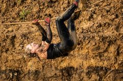 Gijon, Asturias, Spain - February 04, 2019. Trail running female athlete crossing the dirty puddle in aracer by using ropes royalty free stock images