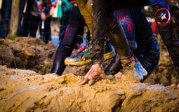 Gijon Asturias, Spanien - Februari 04, 2019 Körande idrottsman nenkorsning för slinga den smutsiga pölen i en gyttjaracerbil fotografering för bildbyråer