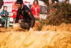 Gijon Asturias, Spanien - Februari 04, 2019 Körande idrottsman nenkorsning för slinga den smutsiga pölen i en gyttjaracerbil arkivfoton