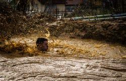 Gijon, Asturies, Espagne - 4 février 2019 : Une éclaboussure de coureur après avoir sauté dans le puits au coureur de boue photographie stock