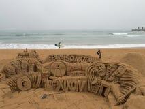 GIJON SPANIEN - OKTOBER 24, 2015: Surfaren går bak sandscuen Royaltyfria Bilder