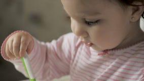 Gil bonito do beb? que senta-se na cadeira de alimenta??o e comer o alimento saud?vel na cozinha video estoque