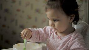 Gil bonito do beb? que senta-se na cadeira de alimenta??o e comer o alimento saud?vel na cozinha filme