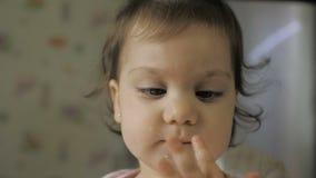 Gil sveglio del bambino che si siede mangiare e nella sedia di alimentazione alimento sano sulla cucina video d archivio
