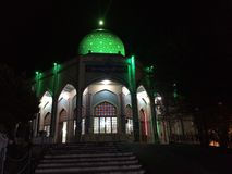 Gilan, Iran - summer, 2018: The shrine of Imam Zadeh Hashem outside the city of Gilan, green light dome in the dark of the night stock images