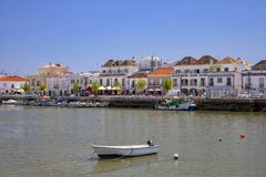 Gilao River flowing through Tavira in Portugal. The Gilao River flowing through the picturesque town of Tavira in Portugal. The tree lined waterfront features stock photos