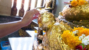 Gild gold cover leaf to Buddist statue. Thai tradition of gild gold cover leaf to Buddist statue at temple in Visakha Bucha day - the most important memorial day royalty free stock photography