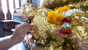 Gild gold cover leaf to Buddist statue. Thai tradition of gild gold cover leaf to Buddist statue at temple in Visakha Bucha day - the most important memorial day stock photo