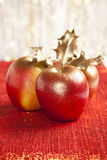 Gilded apples and holly bush on glitter red Royalty Free Stock Images