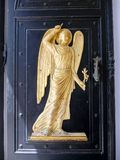 Gilded Angel Figure, Our Lady of Tinos Church, Greece. A gilded bas relief angel religious figure on a black wooden door, Our Lady of Tinos Church, on Tinos, a royalty free stock photos