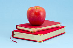 Gilded business diary and red apple Stock Photos