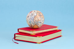 Gilded business diary with small earth globe Stock Photos