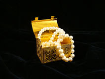 Gilded chest with pearl necklaces. On black velvet Stock Image
