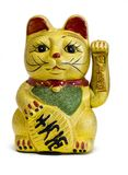 Gilded Chinese Asian or Feng Shui lucky charm cat with a paw raised in greeting denoting wealth and prosperity over a white backgr. The Maneki- Neki Cat is stock photo