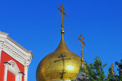 Gilded dome and cross of Russian Orthodox Church. Against the background of the blue sky and a shadow from a cross on a dome royalty free stock images
