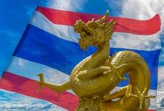 Gilded dragon statue with Thai Flag background. Composite image. Gilded dragon statue in queen sirikit garden phuket with translucent Thai flag as background Stock Photos