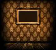 Gilded Frame on Vintage Wallpaper. An empty carved gilded frame on vintage wallpaper Stock Photography