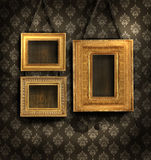 Gilded frames on antique wallpaper