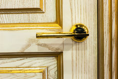 Gilded handle on beige door Royalty Free Stock Photo