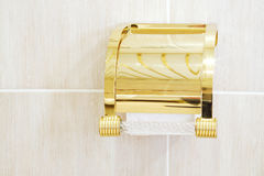 Gilded holder with roll of soft toilet paper in bathroom. Stock Photography