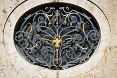 Gilded iron work, architectural detail. MUNICH, GERMANY - Golden decor and wrought iron artwork decorating a round window of the baroque Nymphenburg palace royalty free stock images