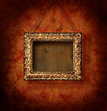 Gilded picture frame on antique wallpaper. Background Royalty Free Stock Image