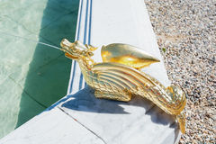 A gilded water spitting dragon as fountain decoration. A gilded water spitting dragon as fountain decoration in The Loo park in Apeldoorn, Netherlands Royalty Free Stock Images