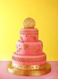 Gilded wedding cake. Pink wedding cake on pink table on yellow backgrounds stock photography
