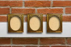 Gilded wooden frames for pictures on old brick wall Stock Photos