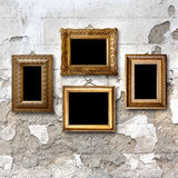 Gilded wooden frames for pictures on stone wall Stock Image