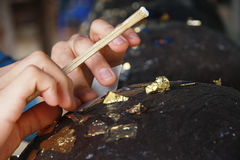 Gilding gold leaf to round stones embedded for worship Buddha. Stock Photos