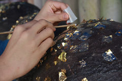 Gilding gold leaf to round stones embedded for worship Buddha. Royalty Free Stock Images