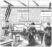 Gilding room at the printing company. Engraving of workers at a printing company appliying the gold gilt edging to the pages of books. From The Harper Stock Image