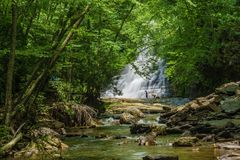 Swimmers at the Base of Cascades Falls, Giles County, Virginia, USA. Giles County, VA – June 1st: Two swimmers at the base of Cascades Falls located in Stock Photos