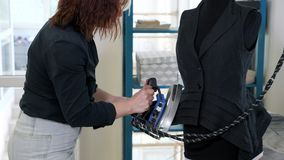Gilet repassant fonctionnant sans couture sur le mannequin avec la vapeur en travaillant l'atelier banque de vidéos