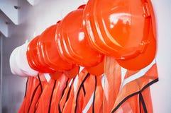 Gilets oranges de sécurité et casques de sécurité oranges Image libre de droits