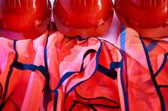 Gilets oranges de sécurité et casques de sécurité oranges Photos libres de droits