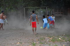 GILI ASAHAN,印度尼西亚- 2016年8月, 22 -男孩踢足球在棕榈树领域的日落靠近海滩 免版税库存照片