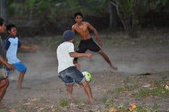GILI ASAHAN,印度尼西亚- 2016年8月, 22 -男孩踢足球在棕榈树领域的日落靠近海滩 库存照片