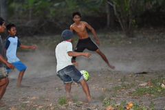 GILI ASAHAN, INDONÉSIA - AGOSTO, 22 2016 - meninos estão jogando o futebol no por do sol em um campo da palmeira perto da praia Fotos de Stock
