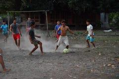 GILI ASAHAN, INDONÉSIA - AGOSTO, 22 2016 - meninos estão jogando o futebol no por do sol em um campo da palmeira perto da praia Imagem de Stock