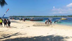 Gili Trawangan, Indonesië, 20 brengt 2019 in de war - Toeristen die op Zandig strand met boten van Gili Trawangan, Indonesië, 4k  stock videobeelden