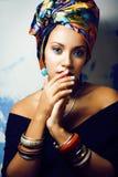 Gillar den ljusa afrikanska kvinnan för skönhet med idérikt smink, sjal på huvudet cubian le för closeup arkivbild