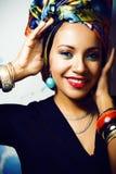 Gillar den ljusa afrikanska kvinnan för skönhet med idérikt smink, sjal på huvudet cubian le för closeup royaltyfri foto
