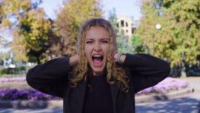 Gillende blondevrouw die haar oren behandelen met gesloten ogen in het park stock videobeelden