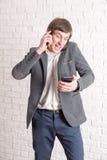Gillende gekke mens met verscheidene telefoons Stock Foto's