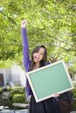 Gillende Gemengde Ras Vrouwelijke Student Holding Blank Chalkboard Stock Foto