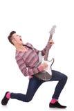 Gillende jonge gitarist die zijn gitaar speelt Stock Fotografie