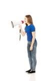 Gillende jonge vrouw met megafoon Stock Foto