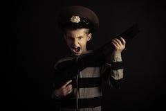 Gillende Jongen met de Holdingsgeweer van de Politiehoed Stock Afbeelding